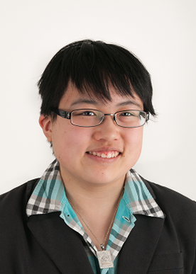 Headshot of Lydia X. Z. Brown, a young Asian American woman with short black hair and rectangular eyeglasses. She is wearing a black jacket and green plaid shirt in this photo.