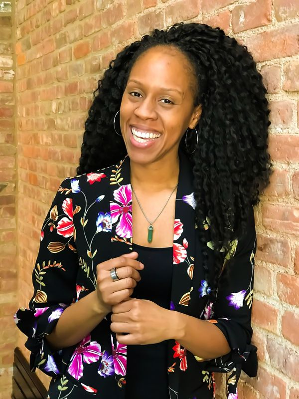 An above-the-waist shot of Storm Smith, a black woman with medium-length curly black hair and a big smile. She is wearing a black tee with a black-and-floral jacket.